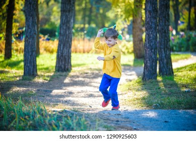 Happy kid playing with toy airplane against blue summer sky background. Boy throw foam plane in the forest or park. Best childhood concept.