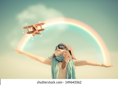 Happy kid playing with toy airplane against summer sky background