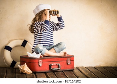 Happy kid playing with toy sailing boat indoors. Travel and adventure concept. Child, summer, vacation