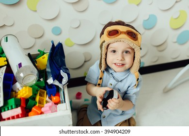 Happy kid playing with toys. Child having fun at home. Young pilot indoors at fun background. Boy in hat like a helmet looking at camera.