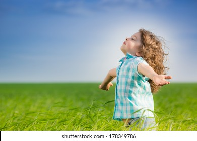 Happy kid with raised arms in green spring field against blue sky. Freedom and happiness concept