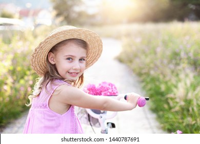 Happy kid is riding on bicycle with flowers on country field road. Child girl in straw hat and pink dress is smiling, having fun. Little lady has fun in summer holidays at sunset.
