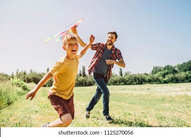 Happy kid is running on field. He is holding thread from kite. Father is holding kite. He is trying to run it to the sky. They are enjoying the moment.