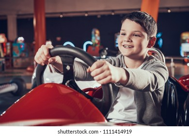 Happy kid sittng in toy car in amusement center. Spending holiday together with family. Entertainment center, mall, amusement park. Family rest, leisure concept.