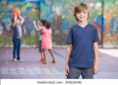 Happy kid smiling in schoolyard with other chilldren playing on background.