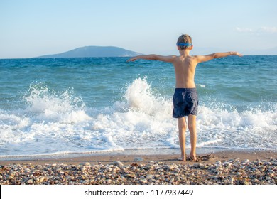 Happy kid is standing at the shoreline watching the waves with open arms.