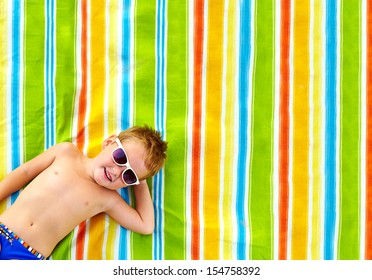 happy kid sunbathing on colorful blanket