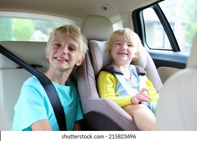 Happy kids, adorable toddler girl with teenager brother sitting together in modern car locked with safety belts enjoying family vacation trip on summer weekend