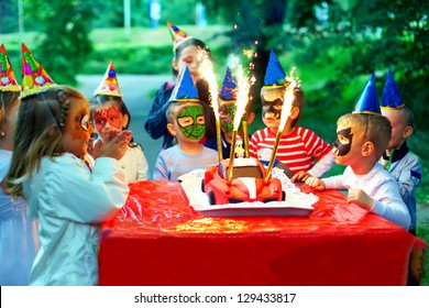happy kids around birthday cake