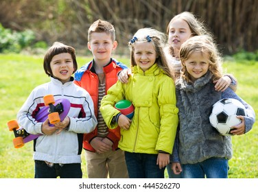 Happy kids with ball having fun outdoors in sunny day