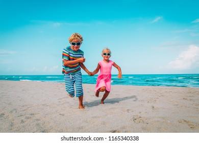 happy kids- boy and girl -running on beach