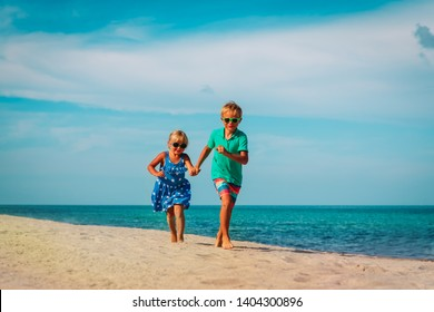 happy kids- boy and girl running at beach