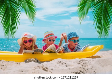 happy kids- boy and girls read books on beach, family vacation