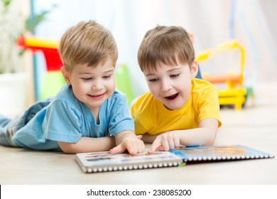 happy kids boys brothers reading together at home