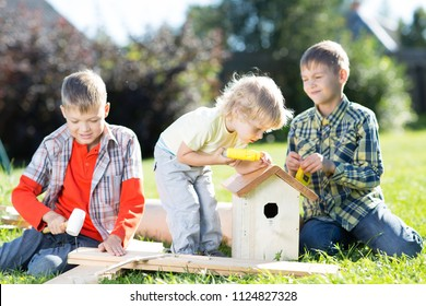 Happy kids boys brothers tinkering sitting on green lawn outdoors