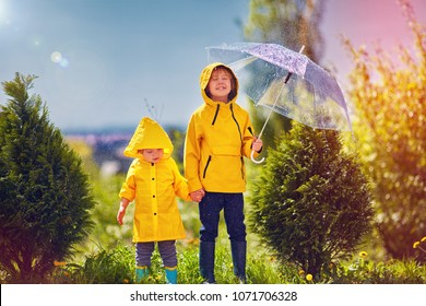 happy kids, brother having fun under the spring sunny rain