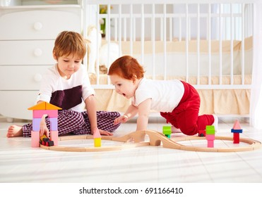 happy kids, brothers playing together with wooden toy railway in nursery room
