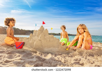 Happy kids building big sand castle on the beach