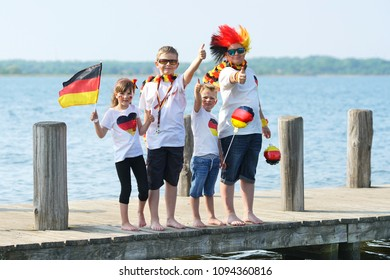 happy kids celebrating their soccer team, german fans at the lake - public viewing