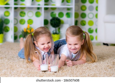 Happy kids daughters drinking milk at home. Parent and children. Beautiful family model.