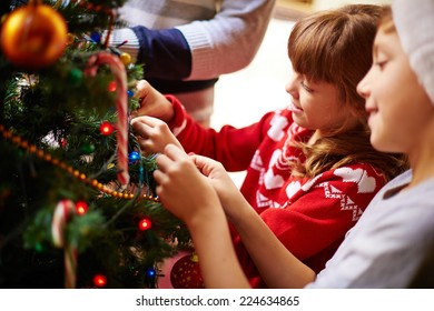 Happy kids decorating Christmas tree for holiday