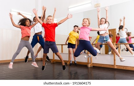 Happy kids of different nationalities and ages jumping during class in dance school