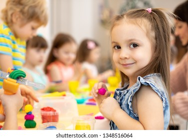 happy kids doing arts and crafts in daycare centre