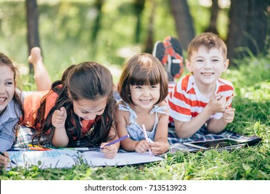 Happy kids doing arts and crafts together in park