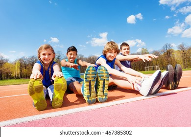 Happy kids doing stretching exercises on a stadium