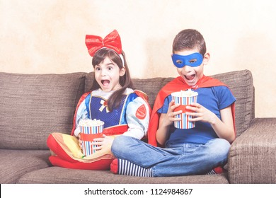 Happy kids dressed up as super heroes and fantasy characters watching TV