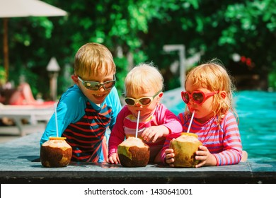 happy kids drinking coconut cocktail on beach resort