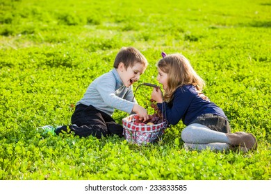 happy kids eating fruits from picnic basket sitting on the green grass