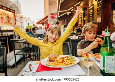 Happy kids eating hamburger with french fries and pizza in outdoor restaurant