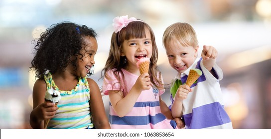 happy kids eating ice cream at a party in cafe