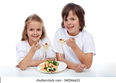 Happy kids eating a pasta dish - isolated