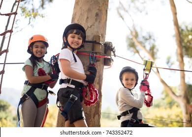 Happy kids enjoying zip line adventure on sunny day