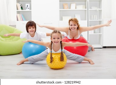 Happy kids exercising with their mother using large rubber balls