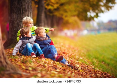 happy kids, friend having fun among fallen leaves in autumn park