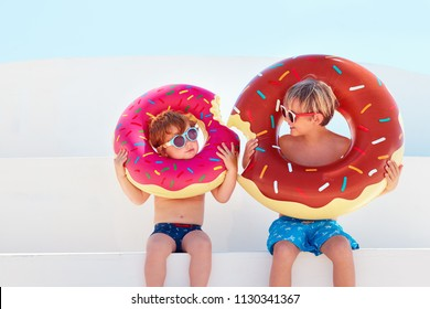 happy kids in glasses and swimming trunks with donut rubber rings ready for summer vacation