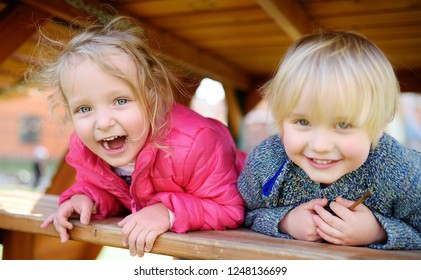 Happy kids having fun on outdoor playground. Spring/summer/autumn active sport leisure for children. Portrait of little boy and girl playing on kindergarten backyard