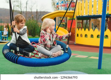 Happy kids having fun on playground outdoors. The best girl friends playing together. Modern colorful playground at park. Playful little girls enjoying at swing. Happy childhood. Family vacation