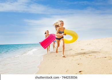 Happy kids having a race on sunny beach in summer