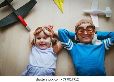 happy kids with helmet and glasses play with toy planes