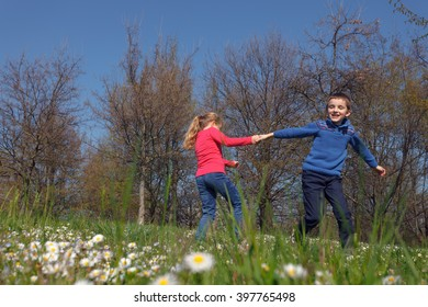 happy kids holding hand and playing on the grass