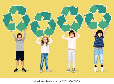 Happy kids holding recycle icons