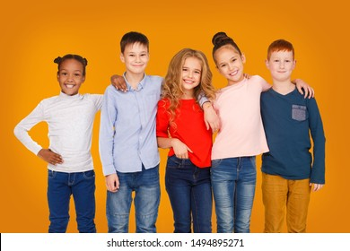 Happy kids hugging and looking at camera against orange background
