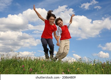 Happy kids jumping against cloudy sky