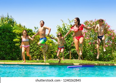 Happy kids jumping into the swimming pool together