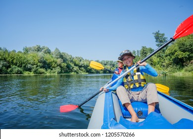 Happy kids kayaking on the river. Active girl with her brother having fun enjoying adventurous experience with kayak on a sunny day during summer vacation
