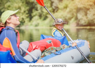 Happy kids kayaking on the river. Active boy with his sister having fun enjoying adventurous experience with kayak on a sunny day during summer vacation